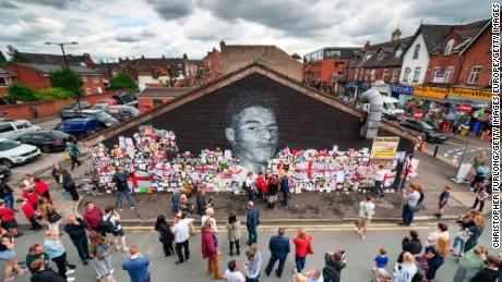 People look at the messages of support and the newly repaired mural of Rashford.