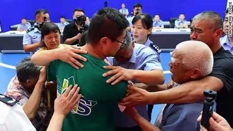 Го Синьчжэнь (в центре) обнимает свою семью на встрече в Ляочэне, Китай, 11 июля.