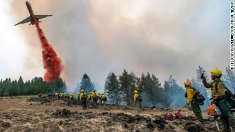 Wildland firefighters watch and take video with their cell phones as a plane drops fire retardant Monday on Harlow Ridge above the Lick Creek Fire, southwest of Asotin, Washington.
