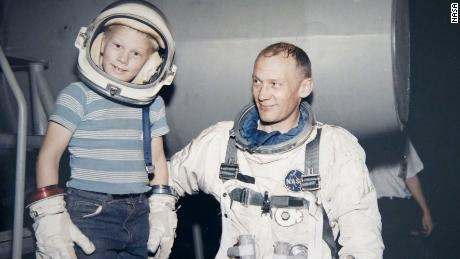 Andy Aldrin tries on his dad's helmet and gloves as Buzz looks on.
