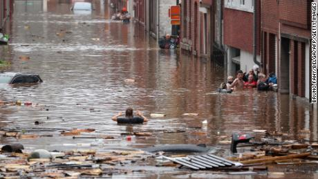 A woman tries to move in a flooded street following heavy rains in Liege, Belgium.