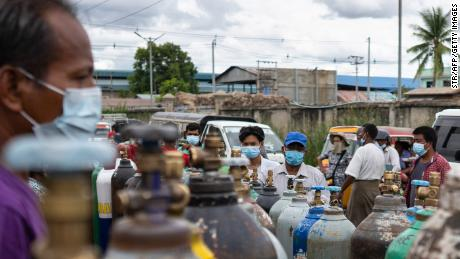 People wait to fill up empty oxygen canisters outside a factory in Mandalay on July 13.