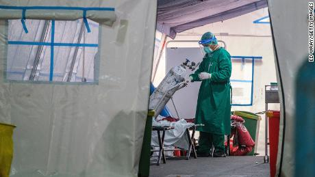 A medical staff changes an oxygen tank in a tent set up in a public hospital to contain the overflow of Covid-19 patients on June 24, 2021 in Jakarta, Indonesia.