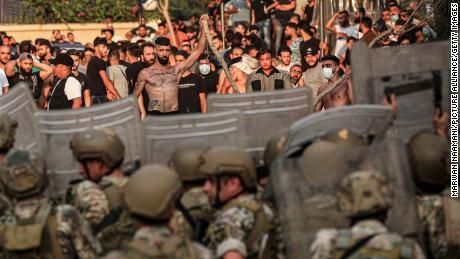 Протестующие противостоят ливанским войскам во время демонстрации после того, как премьер-министр Саад Харири ушел в отставку после того, как не смог сформировать правительство.