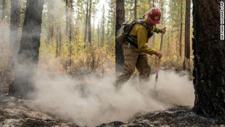Firefighter Garrett Suza, with the Chiloquin Forest Service, mops up a hot spot on the northeast side of the Bootleg Fire, Wednesday, July 14, 2021, near Sprague River, Oregon.