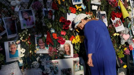 Valerie Flatto visits the memorial bearing photos of some of the victims of the partially collapsed 12-story Champlain Towers South condo building on July 15, 2021 in Surfside, Florida.