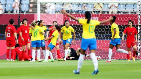 Марта празднует с товарищами по команде, забив первый гол своей команды в ворота Китая.