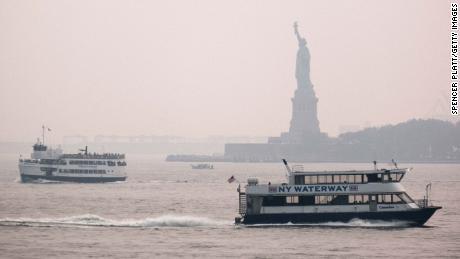 La Estatua de la Libertad se encuentra detrás de una nube de neblina el 20 de julio de 2021 en la ciudad de Nueva York.  Según la Administración Nacional Oceánica y Atmosférica, el humo de los incendios forestales ha llegado al área de los tres estados, lo que crea una disminución de la visibilidad y una neblina amarillenta en muchas áreas.