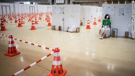 A journalist sits at the Covid-19 testing area of the Olympic media center in Tokyo.