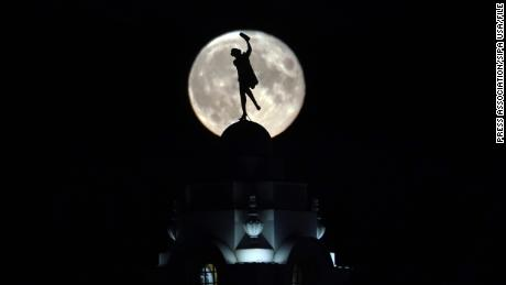 The full buck moon rises over a dancing lady on the Spanish City building in Whitley Bay, England in July 2020.