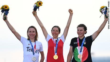 Silver medalist Netherlands' Annemiek Van Vleuten (left), gold medalist Austria's Anna Kiesenhofer (middle) and bronze medalist Italy's Elisa Longo Borghini (right) celebrate on the podium during the women's road race medal ceremony.
