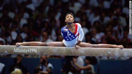 Dominique Dawes stretches on the balance beam at the 1996 Summer Olympics, in Atlanta, Georgia.