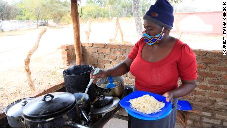 Pauline Chinyandura serves a plate of lunch.