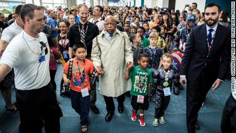 Rep. John Lewis, dressed as his younger self, with Andrew Aydin, his aide and co-author, at right, leads a group of children in a march across the San Diego Convention Center during the 2016 Comic-Con convention.