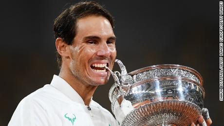Nadal bites the Coupe des Mousquetaires following victory at the French Open.