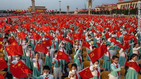 Chinese students wave party and national flags at a ceremony marking the 100th anniversary of the Communist Party at Tiananmen Square on July 1, 2021, in Beijing.