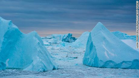 Warmer coastal water melts the Greenland ice sheet around the edges, breaking off massive icebergs that contribute to sea level rise.