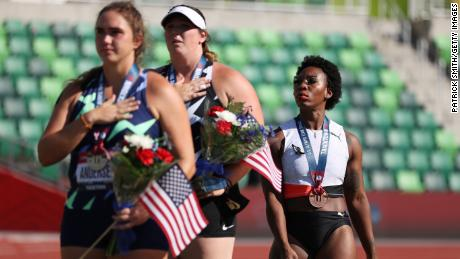 Gwen Berry, right, third place, looks on during the playing of the National Anthem with DeAnna Price, center, first place, and Brooke Andersen, second place, on the podium after the women's Hammer Throw final on day nine of the 2020 US Olympic Track & Field Team Trials at Hayward Field on June 26, 2021, in Eugene, Oregon.