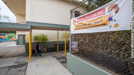 First grade student Daniel Cano, 5, and his mom, Sonia Cano, walk past Covid-19 safety precaution/ social distancing and hand washing signs at a L.A. Unified