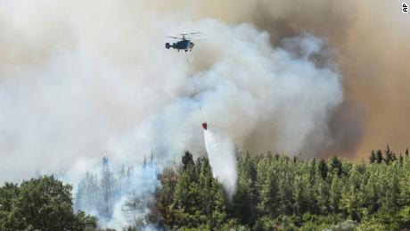 A helicopter fights wildfires in Kacarlar village, near the Mediterranean coastal town of Manavgat, on Saturday, July 31.