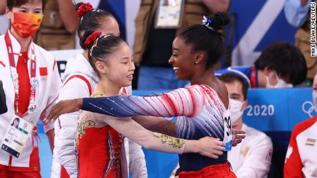 Biles and Guan embrace during the balance beam final.