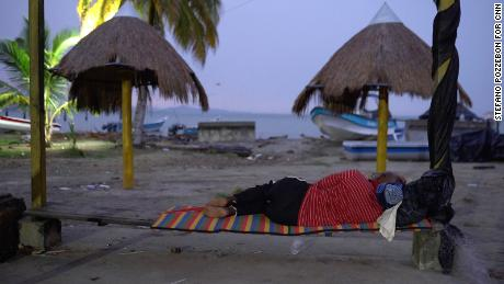 A migrant sleeps on the beach in Necocli on July 31, 2021.