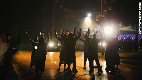 With their hands raised, residents gather at a police line as the neighborhood is locked down following skirmishes on August 11, 2014, in Ferguson, Missouri.