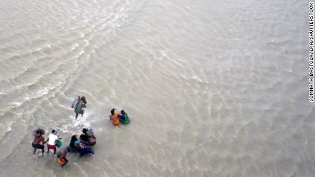 Victims wade through flood water along the Koshi River in Nepal in 2008.