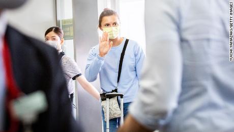 Belarus athlete Kristina Timanovskaya  waves at the boarding gate for Austrian Airlines 0S52 at Tokyo's Narita international airport on August 4.