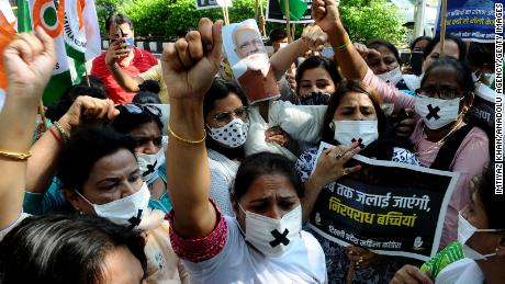 Members of the Indian Congress women's wing carry an effigy of Prime Minister Narendra Modi and Delhi Chief Minister Arvind Kejriwal to burn at a protest on August 3 in New Delhi.