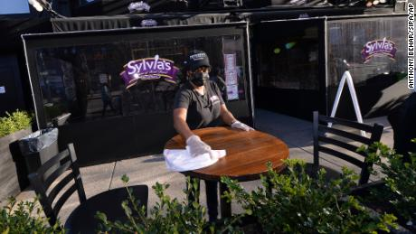 A Sylvia's staff member wipes down an outside table in December 2020.