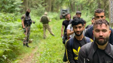 Iraqi migrants walk through the Lithuanian forest.