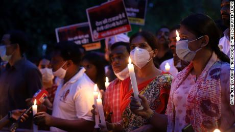 Protesters march with lit candles and placards on August 4 in Delhi, India.