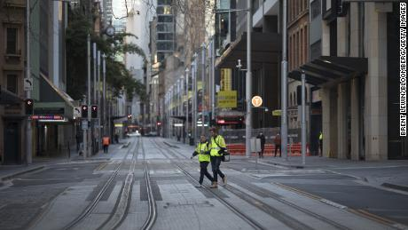 Tradesmen cross a near-empty street in Sydney, Australia, on August 2.