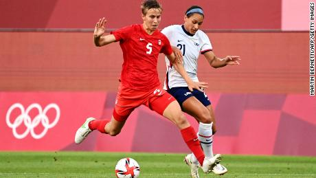 Canada's midfielder Quinn is marked by USA forward Lynn Williams (R) during the Olympic semi match.