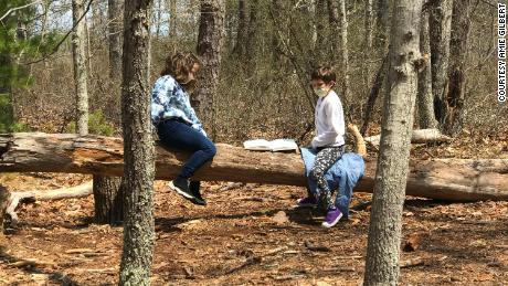 """Emma Casey, left, and Reina Dwyer read to each other from """"Charlotte's Web"""" during outdoor time in Gilbert's class."""