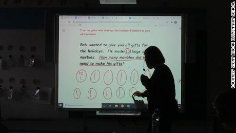 Gilbert teaches students how to solve a word problem during the past school year.