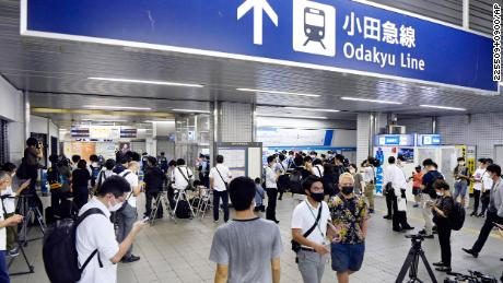 Police and media gather at Soshigaya Okura Station in Tokyo on Friday following the incident.
