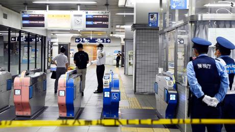 Policemen stand as ticket gates are sealed off at Soshigaya Okura Station after a stabbing on a commuter train in Tokyo on Friday.