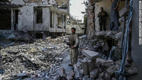 Afghan security personnel inspect the scene of a car bomb explosion in Kabul on August 4