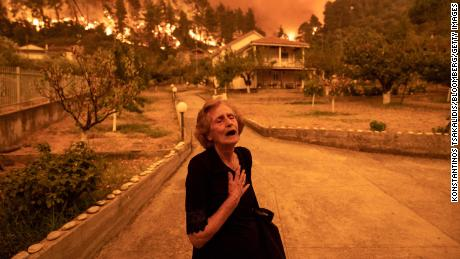 An elderly resident reacts as a wildfire approaches her house in the village of Gouves, on the island of Evia, Greece, on Sunday, Aug. 8, 2021. Thousands of residents were evacuated from the Greek island of Evia by boat after wildfires hit Greeces second biggest island. Photographer: Konstantinos Tsakalidis/Bloomberg via Getty Images