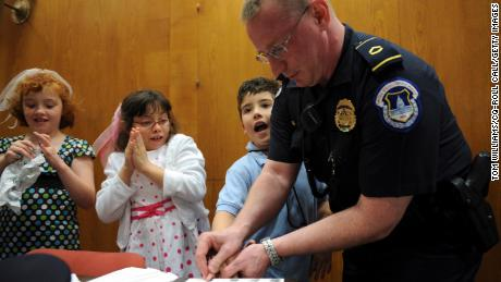 """Capitol Police Officer Howard Liebengood fingerprints a child during """"Kid Safety Day,"""" held in Washington DC, in April 2008. Liebengood died by suicide after the US Capitol riot in January 2021."""