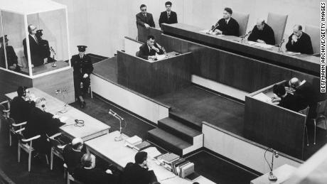 Adolf Eichmann listens in the prisoner's dock at the left, as presiding Judge Moishe Landau gives the verdict at the conclusion of his trial.