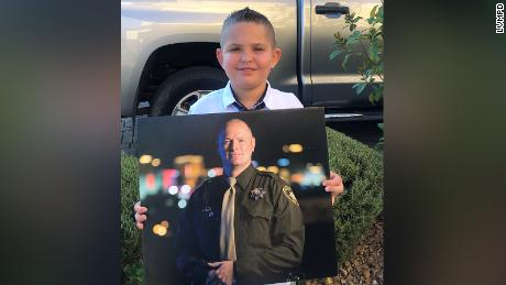 Noah holds a photo of his late father, Officer Jason Swanger.
