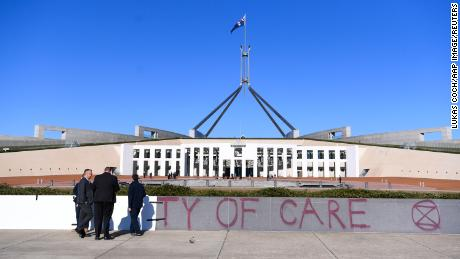 Workers cover the slogan 'Duty of Care' after an Extinction Rebellion protest outside Parliament House, in Canberra, Monday, August 10, 2021. (AAP Image/Lukas Coch) NO ARCHIVINGNo Use Australia. No Use New Zealand.