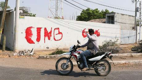 A motorist passes by a wall with a graffiti of the Jalisco New Generation Cartel (CJNG) in El Aguaje after the visit of Vatican's ambassador to Mexico Franco Coppola to the area and to the municipality of Aguililla, an area where the Jalisco New Generation Cartel (CJNG) and local drug gangs are fighting to control the territory, in Michoacan state, Mexico April 23, 2021. REUTERS/Alan Ortega
