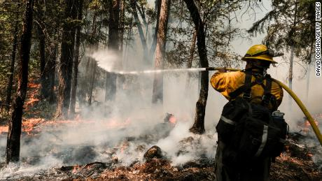 A firefighter extinguishes a control burn, a preventative measure to protect a home located in Greenville, California, on August 9, 2021.