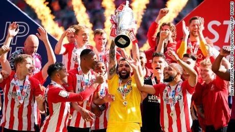 El portero del Brentford, David Raya Martin, levanta el trofeo mientras celebran el ascenso a la Premier League después de ganar la final de los playoffs del campeonato en el estadio de Wembley.