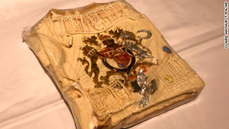 The cake slice features a coat-of-arms colored in gold, red, blue and silver, a silver horseshoe and leaf spray, as well as some white decorative icing.