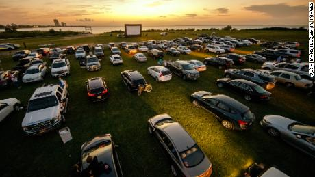 """Attendees arrive to watch the movie """"Grease"""" at a pop-up drive-in theatre at Bucktown Marina Park on May 22, 2020 in Metairie, Louisiana. With indoor theaters in many places closed due to coronavirus, drive-in theaters saw a rise in attendance."""